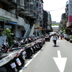 """Typisch: Viele Mopeds und eine Radfahrerin mit """"Sonnenschirm""""."""